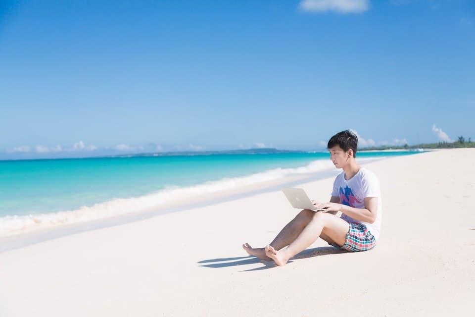 海と男性とノートパソコン